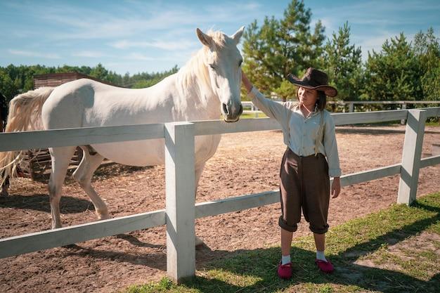 Jovem com roupas vintage em pé com seu cavalo branco brilhante no paddock em um dia ensolarado