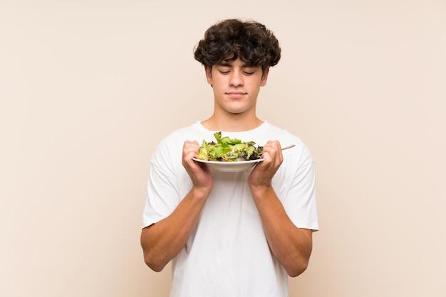 Jovem com salada sobre parede verde isolada