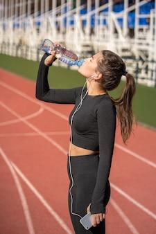 Jovem com sede em forma de mulher bebendo água de uma garrafa de plástico