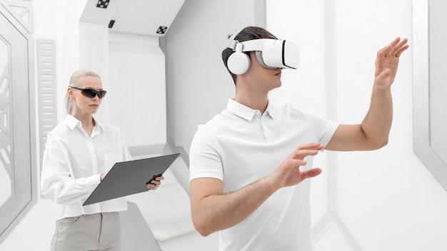 Jovem com simulador de realidade virtual e mulher testando