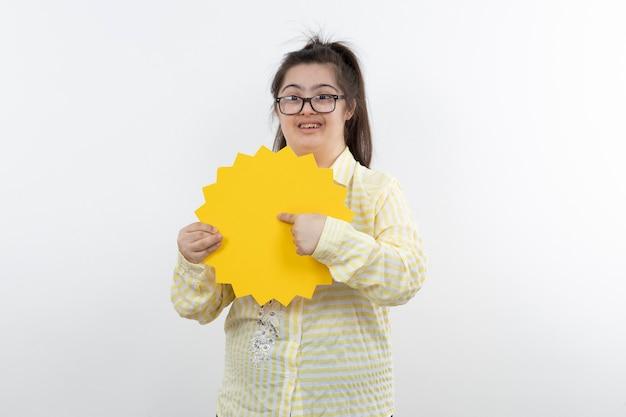 Jovem com síndrome de down com balão amarelo posando.