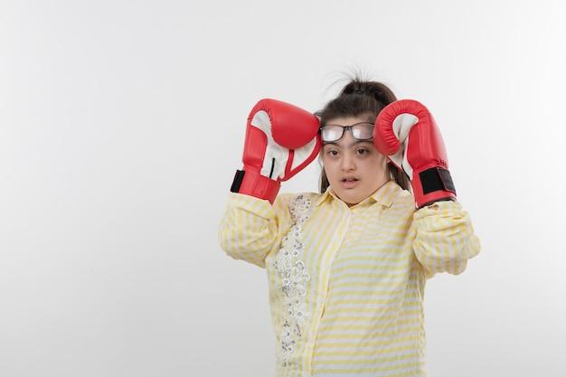 Jovem com síndrome de down vestindo uma camisa xadrez amarela usando luvas de boxe