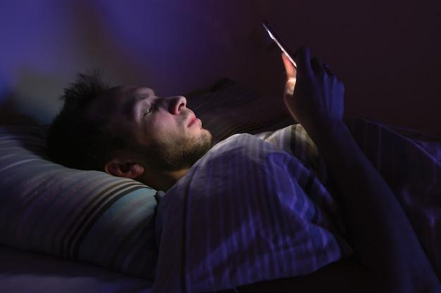 Jovem com sono, deitado na cama, usando o smartphone à noite, não consegue dormir. insônia, melatonina, distúrbio do sono
