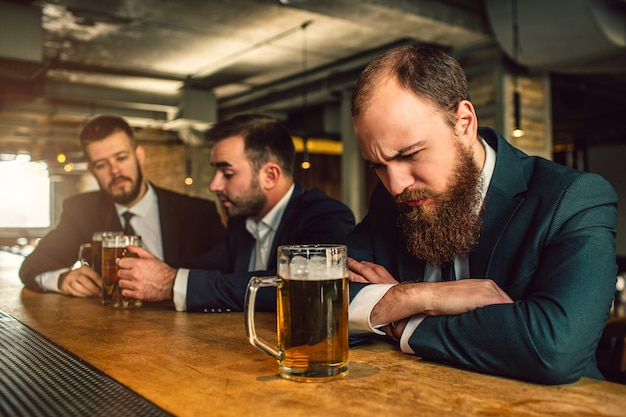 Jovem com sono dorme no balcão do bar. há caneca de cerveja. dois outros homens sentam-se atrás e conversam. eles têm caneca de cerveja dois.