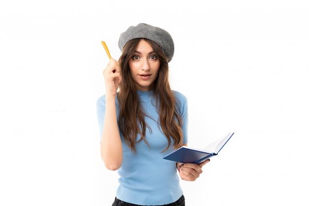 Jovem com sorriso encantador, cabelo castanho longo ondulado, maquiagem linda, em jersey azul, jeans preto, boina cinza, em pé com caneta e caderno