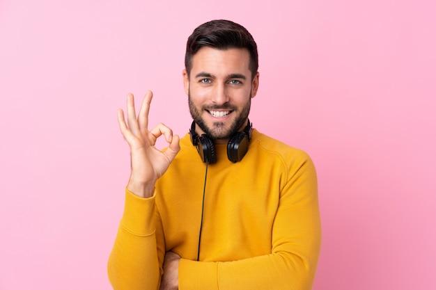 Jovem com suéter amarelo, fazendo um gesto ok
