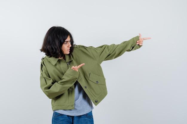 Jovem com suéter cinza, jaqueta cáqui, calça jeans apontando para a direita com o dedo indicador, olhando para a direita e olhando com foco, vista frontal.