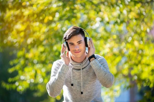 Jovem com suéter cinza no parque com fones de ouvido ouvindo música