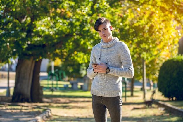 Jovem com suéter cinza no parque com smartphone e fones de ouvido jovem com suéter cinza no parque com telefone celular e fones de ouvido