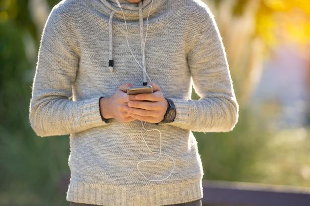 Jovem com suéter cinza no parque com telefone celular