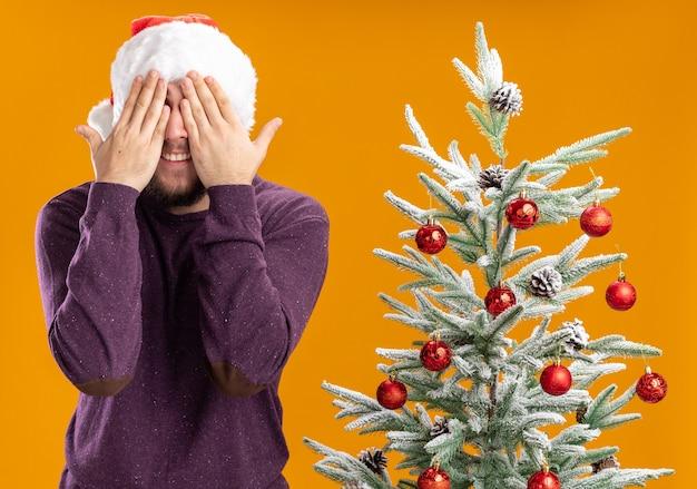 Jovem com suéter roxo e chapéu de papai noel cobrindo os olhos com as mãos ao lado da árvore de natal sobre fundo laranja