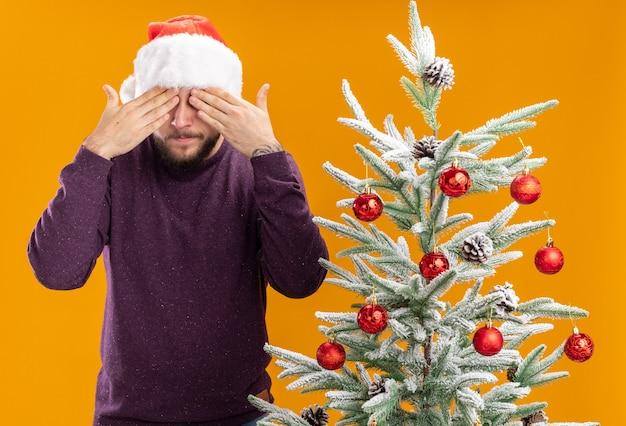 Jovem com suéter roxo e chapéu de papai noel cobrindo os olhos com as mãos em pé ao lado da árvore de natal sobre fundo laranja