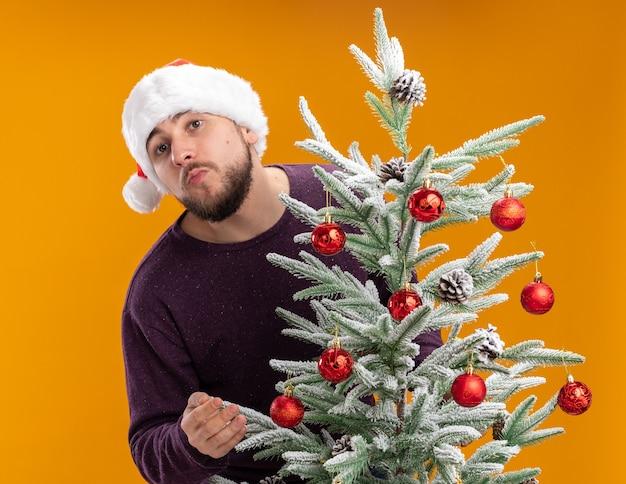 Jovem com suéter roxo e chapéu de papai noel com uma cara feliz ao lado de uma árvore de natal sobre um muro laranja