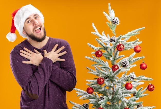 Jovem com suéter roxo e chapéu de papai noel olhando para a câmera com uma cara feliz de mãos dadas no peito ao lado da árvore de natal sobre fundo laranja