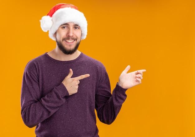 Jovem com suéter roxo e chapéu de papai noel olhando para a câmera, sorrindo alegremente, apontando com o dedo indicador para o lado em pé sobre um fundo laranja