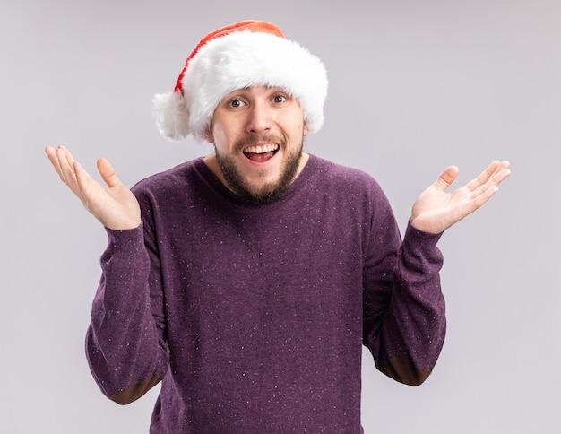 Jovem com suéter roxo e chapéu de papai noel olhando para a câmera, sorrindo confuso, abrindo os braços para os lados, de pé sobre um fundo branco