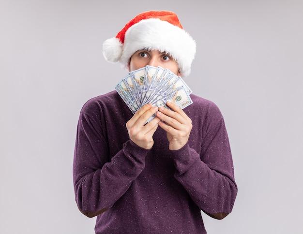 Jovem com suéter roxo e chapéu de papai noel segurando dinheiro cobrindo o rosto com dinheiro olhando de lado preocupado em pé sobre um fundo branco