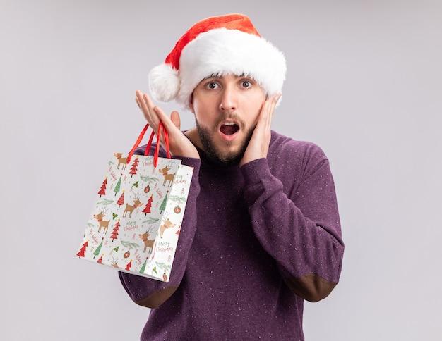 Jovem com suéter roxo e chapéu de papai noel segurando um saco de papel de presente, olhando para a câmera espantado e surpreso em pé sobre um fundo branco