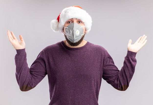 Jovem com suéter roxo e chapéu de papai noel usando máscara protetora facial, olhando para a câmera, confuso, espalhando as mãos para os lados sem resposta, de pé sobre um fundo branco