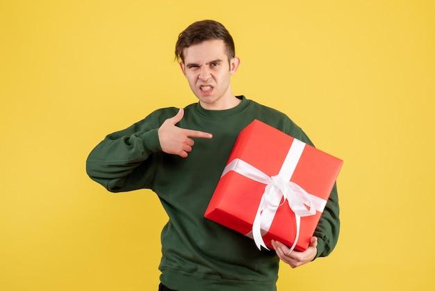Jovem com suéter verde apontando para um presente em amarelo de frente