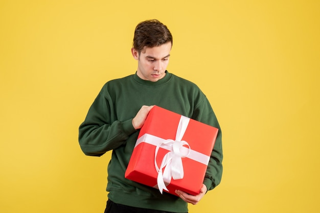 Jovem com suéter verde olhando para um presente em amarelo de frente