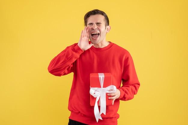 Jovem com suéter vermelho gritando no espaço de cópia de fundo amarelo