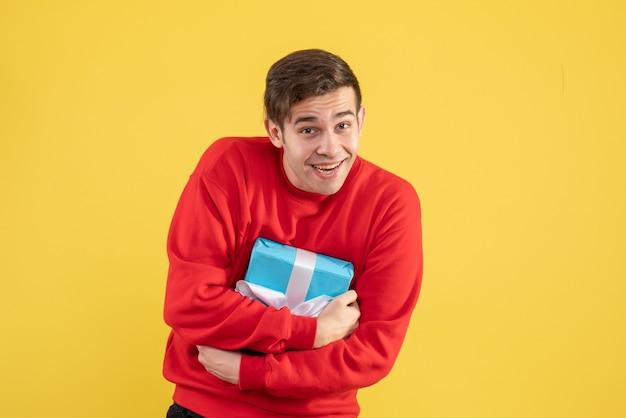 Jovem com suéter vermelho segurando seu presente com força sobre fundo amarelo.