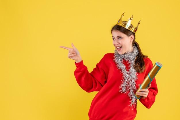 Jovem com suéter vermelho segurando uma pipoca apontando com o dedo algo