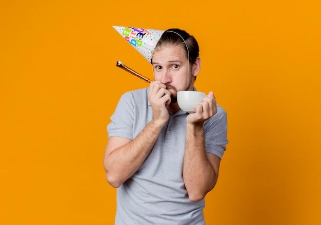 Jovem com tampa de feriado comemorando festa de aniversário segurando uma tampa de café, parecendo surpreso e confuso em pé em frente à parede laranja