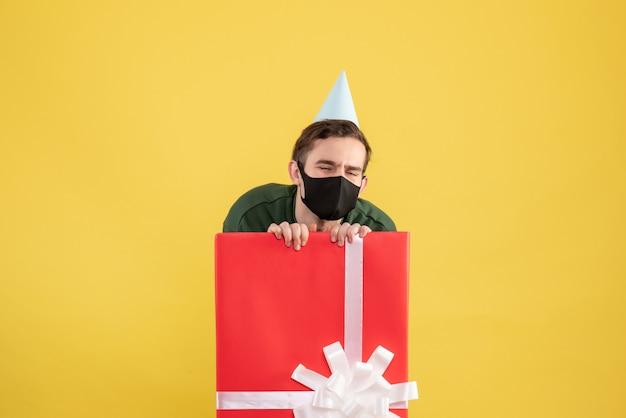 Jovem com tampa de festa se escondendo atrás de uma grande caixa de presente em fundo amarelo de frente