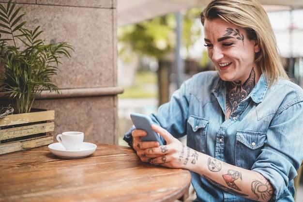 Jovem com tatuagens usando o celular em uma cafeteria