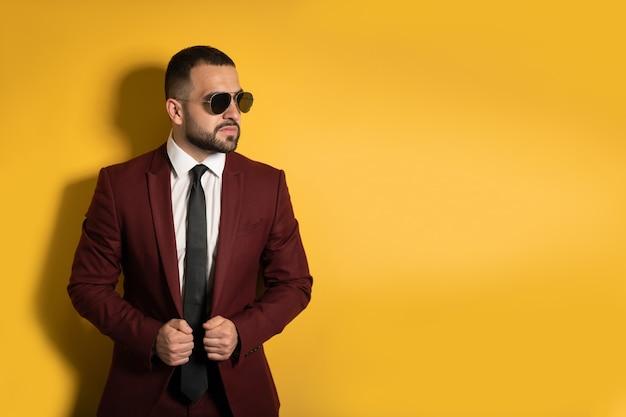 Jovem com terno cor de vinho olhando seriamente de lado usando óculos escuros e as mãos segurando uma jaqueta isolada na parede amarela
