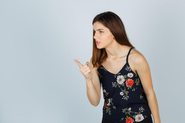 Jovem com top floral mostrando gesto de advertência