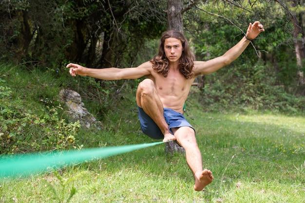 Jovem com torso nu, equilibrando no slackline em campo verde no verão
