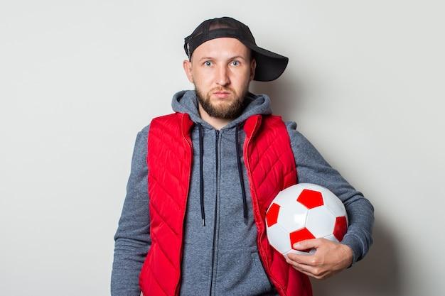 Jovem com um boné vestido de maneira casual, moletom com capuz e colete segurando uma bola de futebol contra uma parede de luz