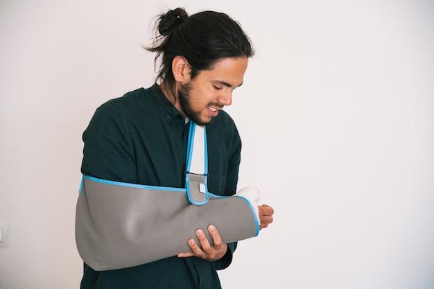 Jovem com um braço enfaixado e uma tipoia de tecido segurando seu braço com uma expressão de dor