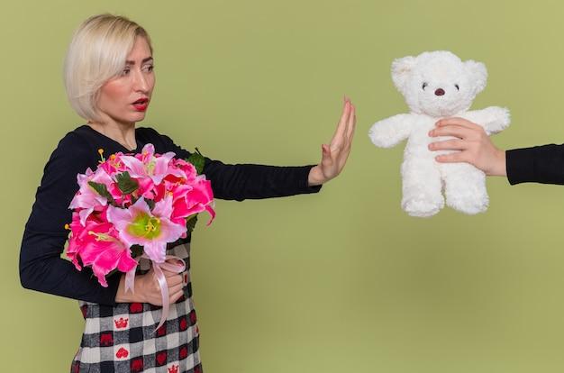 Jovem com um buquê de flores, parecendo confusa, fazendo gesto de pare enquanto recebe o ursinho de presente