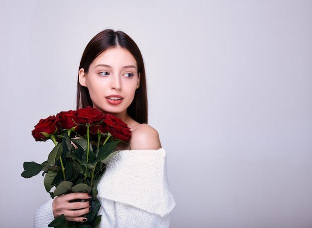 Jovem com um buquê de rosas vermelhas.