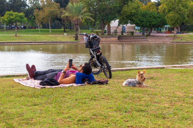 Jovem com um cachorro descansando no parque.