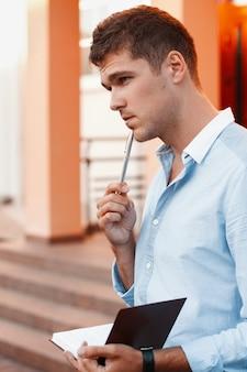 Jovem com um caderno e uma caneta pensando no trabalho