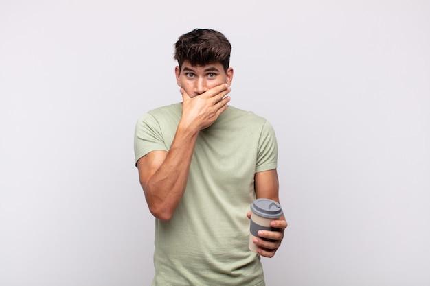 Jovem com um café cobrindo a boca com as mãos com uma expressão chocada e surpresa, mantendo um segredo ou dizendo oops