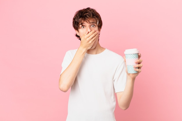 Jovem com um café cobrindo a boca com as mãos em choque