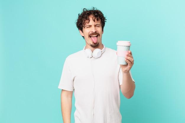 Jovem com um café com atitude alegre e rebelde, brincando e mostrando a língua