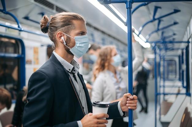 Jovem com um café para viagem de pé em um vagão do metrô