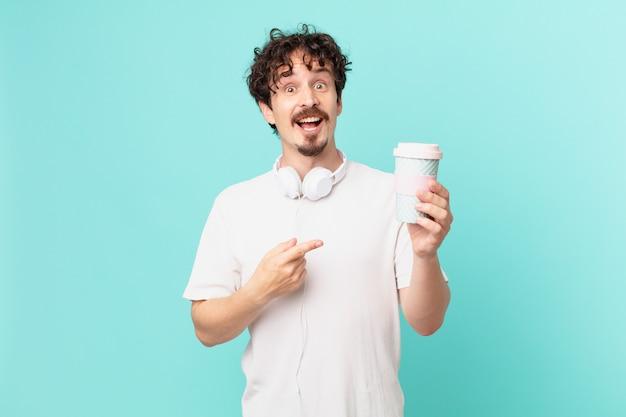 Jovem com um café, parecendo animado e surpreso, apontando para o lado