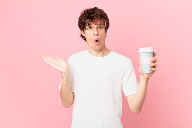 Jovem com um café parecendo surpreso e chocado, com o queixo caído segurando um objeto