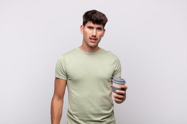 Jovem com um café se sentindo perplexo e confuso, com uma expressão muda e atordoada olhando para algo inesperado