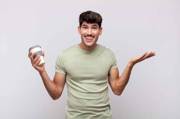 Jovem com um café sentindo-se feliz, animado, surpreso ou chocado, sorrindo e surpreso com algo inacreditável