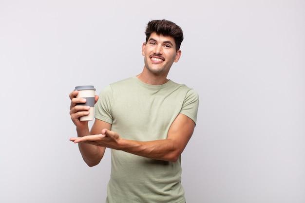Jovem com um café sorrindo alegremente, sentindo-se feliz e mostrando um conceito no espaço da cópia com a palma da mão