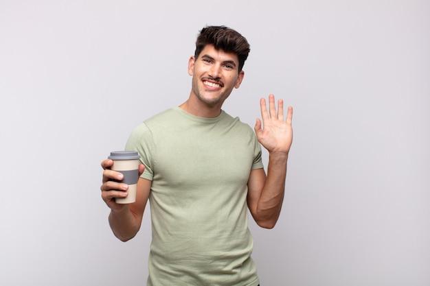 Jovem com um café sorrindo feliz e alegre, acenando com a mão, dando as boas-vindas e cumprimentando ou dizendo adeus
